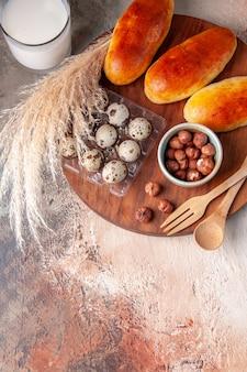 Vue de dessus de délicieux petits pains cuits au four avec un verre de lait sur une surface légère repas pâtisserie gâteau nourriture four couleur pâte tarte