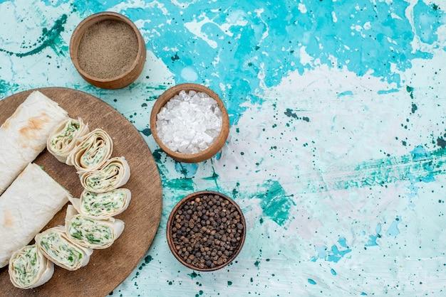 Vue de dessus de délicieux petits pains de légumes entiers et tranchés avec des légumes verts et des assaisonnements sur le bureau bleu vif de légumes