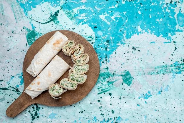 Vue de dessus de délicieux petits pains de légumes entiers et tranchés avec des verts sur le fond bleu-lumineux de couleur végétale