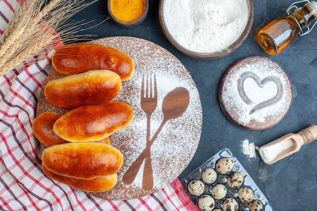 Vue de dessus de délicieux petits pains sur planche de bois oeufs de caille bouteille d'huile bol de farine de curcuma sur fond sombre