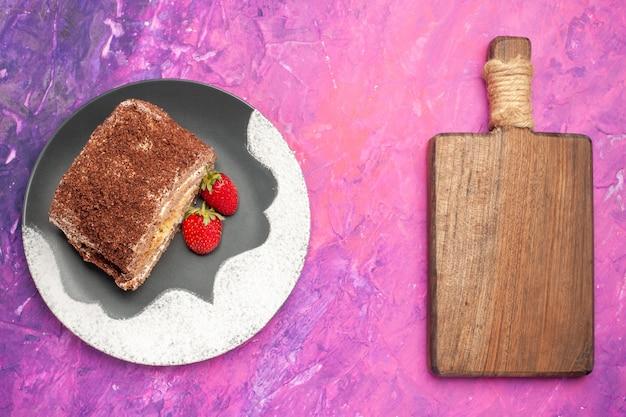 Vue de dessus de délicieux petits pains sucrés aux fraises sur une surface rose clair