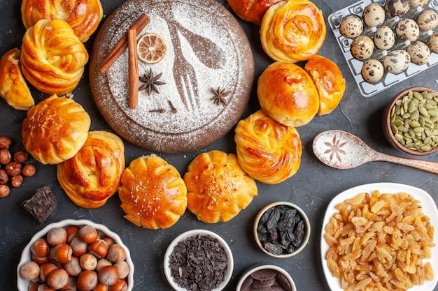 Vue de dessus de délicieux petits pains sucrés aux noix et aux raisins secs sur fond sombre