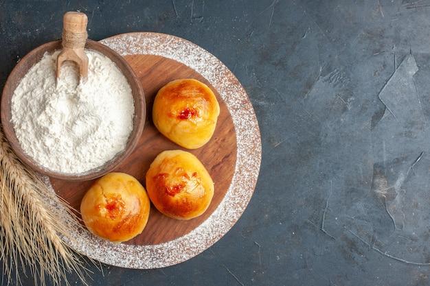 Vue de dessus de délicieux petits pains sucrés avec de la farine sur fond sombre