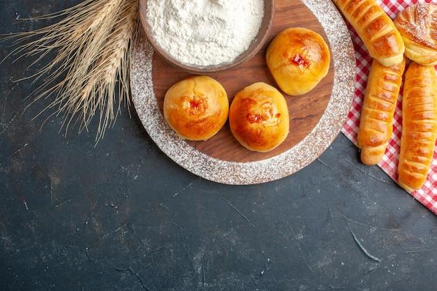 Vue de dessus de délicieux petits pains sucrés avec de la farine et de la gelée sur fond sombre