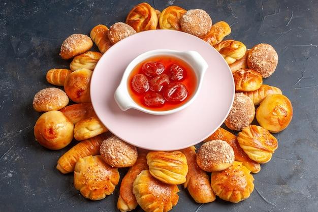 Vue de dessus de délicieux petits pains sucrés avec de la gelée sur fond sombre