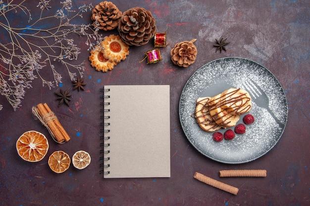 Vue de dessus de délicieux petits pains sucrés tranchés de bonbons pour le thé à l'intérieur de la plaque sur fond sombre rouleaux de pâte à biscuits gâteau sucré