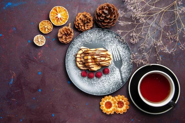 Vue de dessus de délicieux petits pains sucrés en tranches de gâteau pour une tasse de thé sur le fond sombre rouleau biscuit tarte sucrée gâteau au thé dessert