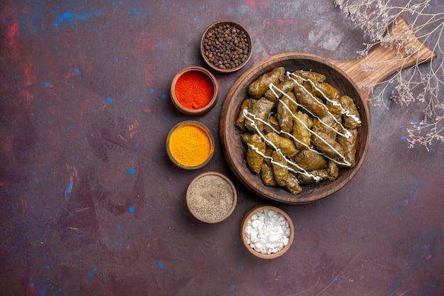 Vue de dessus délicieux plat de viande dolma avec différents assaisonnements sur fond sombre nourriture calorie plat dîner viande