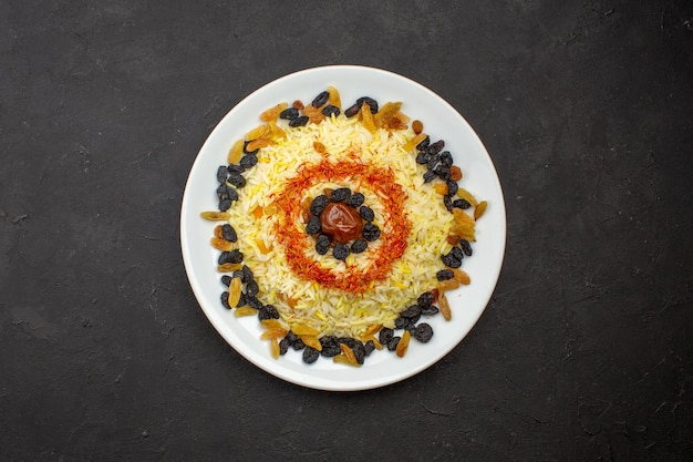 Vue de dessus de délicieux plov avec de l'huile et des raisins secs à l'intérieur de la plaque sur l'espace sombre