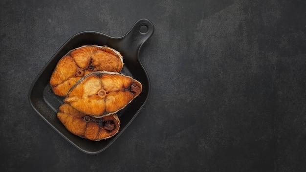 Vue de dessus d'un délicieux poisson frit avec une poêle noire sur fond de texture de ton sombre