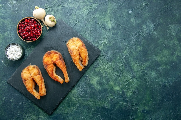 Vue de dessus délicieux poisson frit sur la surface sombre plat salade fruits de mer océan viande poivre de mer nourriture eau repas espace libre