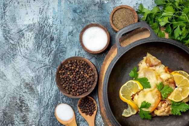 Vue de dessus de délicieux poissons frits au citron et au persil dans une poêle sur une planche de bois