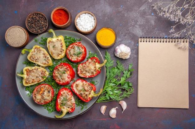 Vue de dessus de délicieux poivrons délicieux repas cuisinés avec des légumes verts et des assaisonnements sur le plat de surface sombre dîner repas