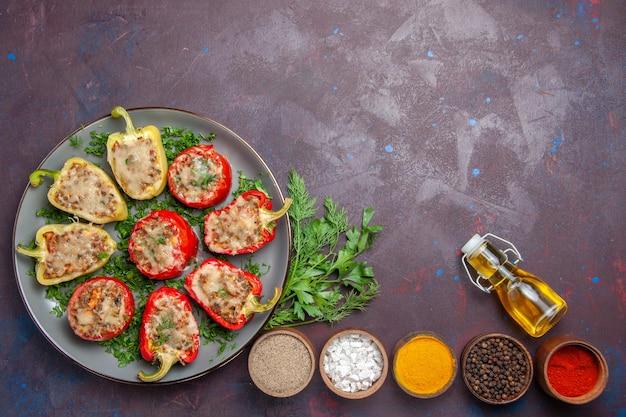 Vue de dessus de délicieux poivrons délicieux repas cuisinés avec de la viande et des légumes verts sur un plat de surface sombre dîner repas