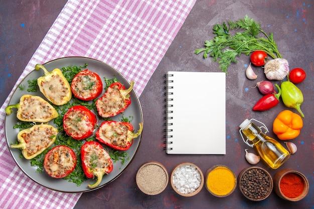Vue de dessus de délicieux poivrons délicieux repas cuisinés avec de la viande et des légumes verts sur la surface sombre dîner repas plat de nourriture poivre épicé
