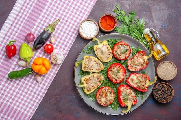 Vue de dessus de délicieux poivrons délicieux repas cuisinés avec de la viande et des légumes verts sur la surface sombre dîner repas plat poivre nourriture épicée