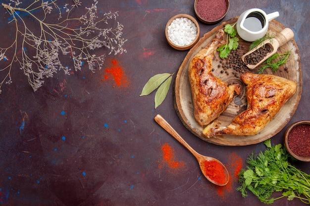 Vue de dessus délicieux poulet frit avec différents assaisonnements sur un bureau sombre