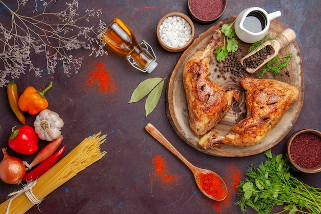 Vue de dessus délicieux poulet frit avec différents assaisonnements sur l'espace sombre