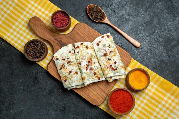 Vue de dessus de délicieux qutabs de tranches de pâte cuites avec des légumes verts et différents assaisonnements sur un espace gris
