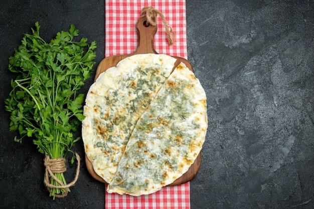 Vue de dessus de délicieux qutabs de tranches de pâte cuites avec des légumes verts frais sur un espace gris