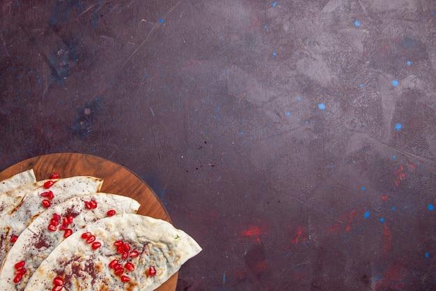 Vue de dessus de délicieux qutabs de viande pitas avec des grenades rouges fraîches sur fond violet foncé repas de pâte de viande pita