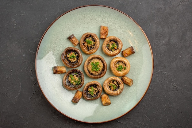 Vue de dessus délicieux repas de champignons cuits avec des légumes verts à l'intérieur de la plaque sur le plat de surface sombre dîner cuisine mûre sauvage
