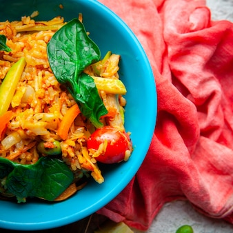 Vue de dessus délicieux repas dans une assiette bleue sur bois, tissu rouge et fond texturé blanc.