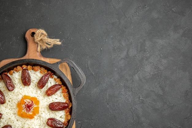 Vue de dessus délicieux repas de riz plov cuit avec khurma et raisins secs sur une surface grise plat de cuisson de riz plov repas
