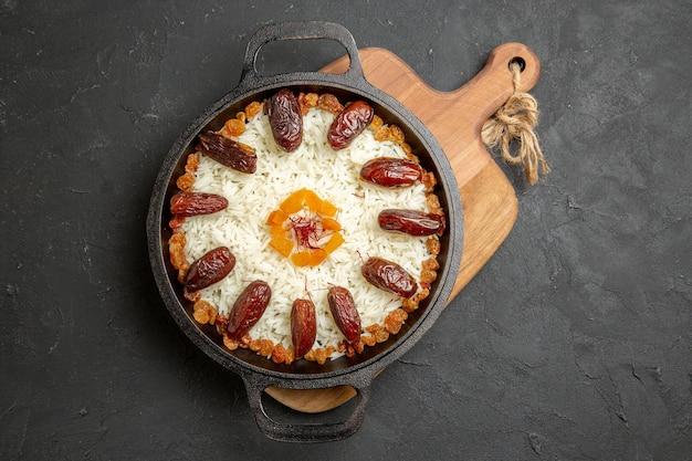 Vue de dessus délicieux repas de riz plov cuit avec khurma et raisins secs sur une surface sombre plat de cuisson de riz plov repas