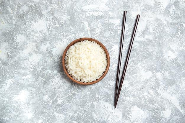 Vue de dessus délicieux riz cuit à l'intérieur de la plaque brune sur blanc