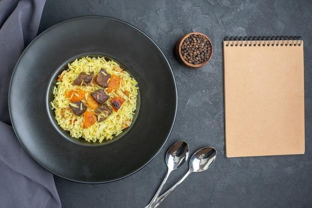 Vue de dessus délicieux riz cuit pilaf avec abricots secs et tranches de viande à l'intérieur de la plaque sur une surface sombre