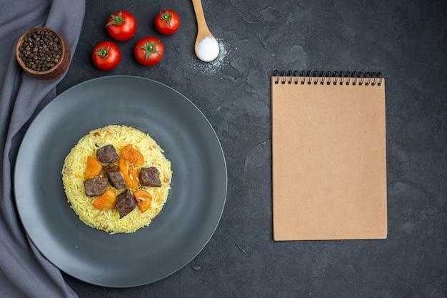 Vue de dessus délicieux riz cuit pilaf avec des tranches de viande et des tomates sur une surface sombre