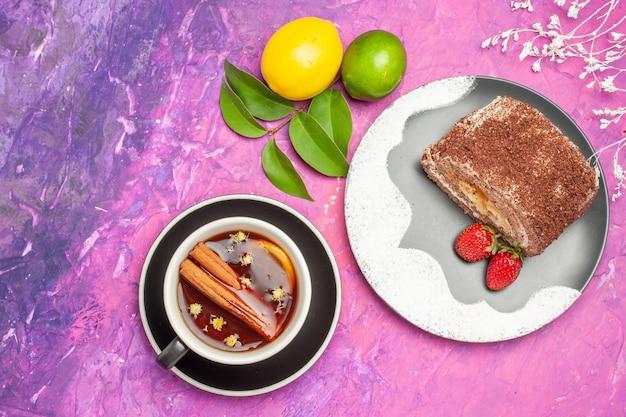 Vue de dessus délicieux rouleau sucré avec tasse de thé sur fond rose