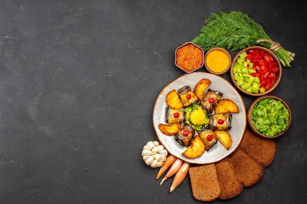 Vue de dessus de délicieux rouleaux d'aubergines plat cuisiné avec des pommes de terre et des miches de pain sur fond sombre cuisson des aliments plat de friture cuire des pommes de terre