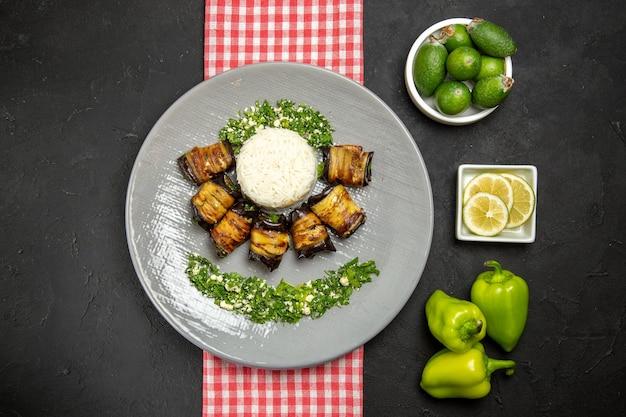 Vue de dessus de délicieux rouleaux d'aubergines plat cuit avec du riz sur la surface sombre cuisson de l'huile végétale de riz cuisine alimentaire