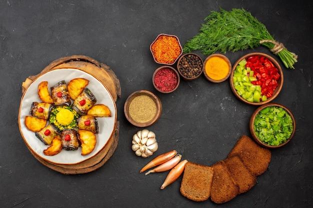 Vue de dessus de délicieux rouleaux d'aubergines plat cuit avec des pommes de terre et des légumes sur le fond sombre cuisson plat de cuisson cuire des pommes de terre frites