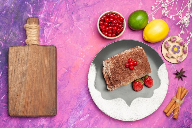 Vue de dessus de délicieux rouleaux de biscuits aux fruits sur un bureau rose