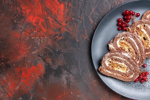 Vue de dessus de délicieux rouleaux de biscuits aux fruits sur un bureau sombre