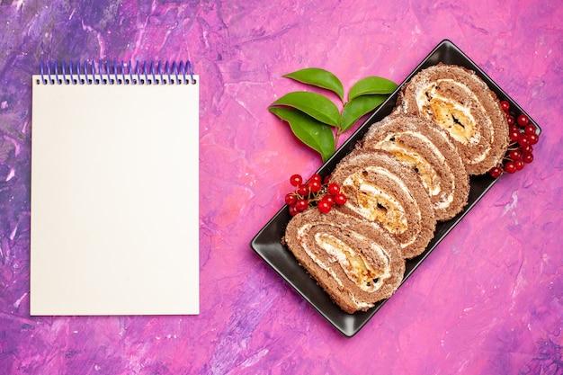 Vue de dessus de délicieux rouleaux de biscuits sur fond rose