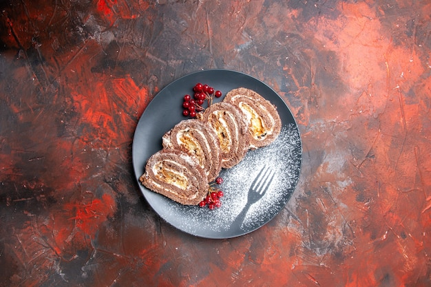 Vue de dessus de délicieux rouleaux de biscuits à l'intérieur de la plaque sur un bureau sombre