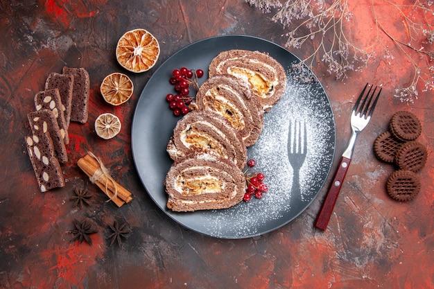 Vue de dessus de délicieux rouleaux de biscuits à l'intérieur de la plaque sur fond sombre