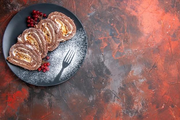 Vue de dessus de délicieux rouleaux de biscuits à l'intérieur de la plaque sur un sol sombre