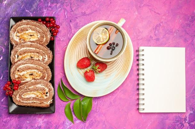 Vue de dessus de délicieux rouleaux de biscuits avec une tasse de thé sur un bureau rose