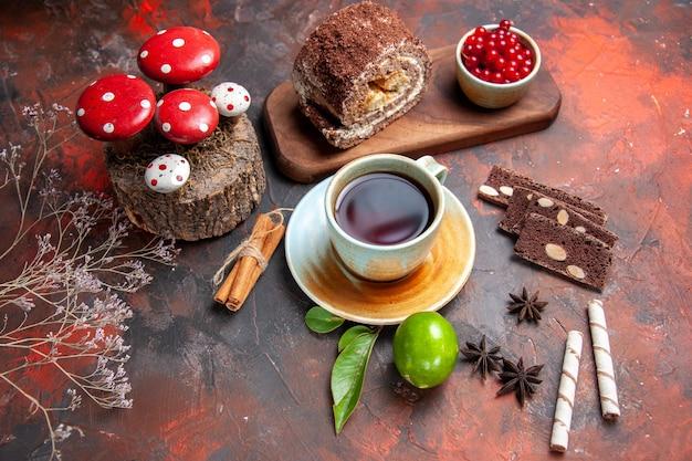 Vue de dessus de délicieux rouleaux de biscuits avec une tasse de thé sur un bureau sombre