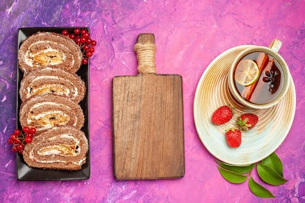 Vue de dessus de délicieux rouleaux de biscuits avec une tasse de thé sur fond rose
