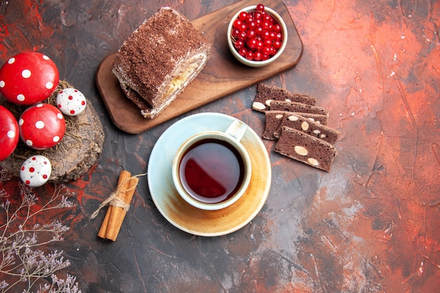 Vue de dessus de délicieux rouleaux de biscuits avec une tasse de thé sur fond sombre