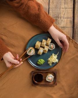 Vue de dessus de délicieux rouleaux de sushi avec des ingrédients sur une table en bois