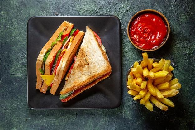 Vue de dessus délicieux sandwich au jambon à l'intérieur de la plaque sombre avec des frites et du ketchup sur une surface sombre