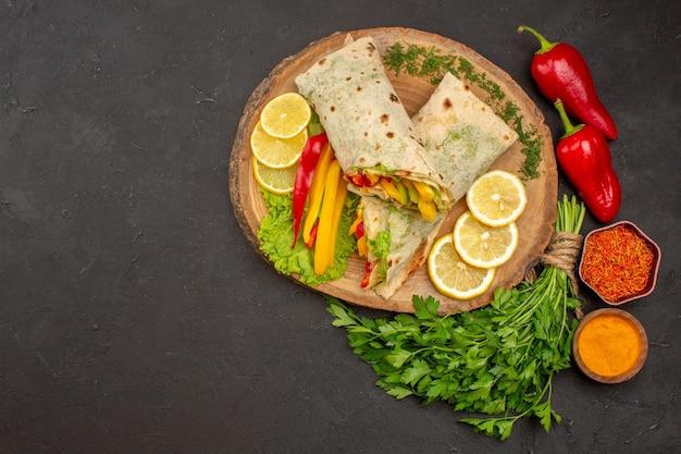 Vue de dessus d'un délicieux sandwich au poulet tranché shaurma avec des verts de citron sur l'obscurité