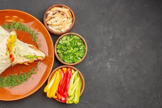 Vue de dessus délicieux sandwich à la salade de shaurma en tranches avec des verts sur fond sombre burger repas sandwich pain collation